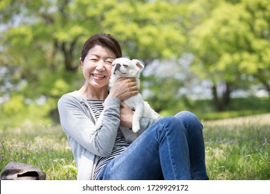 A Japanese middle-aged woman holding a pet dog