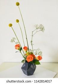 Japanese miniature style flower arrangement or ikebana,Orange mini rose and golden stick arranged in round shaped black vase.