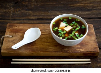 Japanese miso soup in ceramic bowl on dark wooden background, copy space. Asian miso soup with tofu.