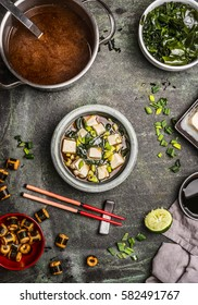 Japanese miso soup with ingredients: wakame seaweed, Silken tofu,  and spring onions, served in bowl on table with chopsticks, top view