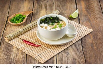Japanese miso soup with wakame, tofu cheese and egg in a white bowl on the table covered with bamboo mat. Copy space