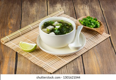 Japanese miso soup in a white bowl on the table covered with bamboo mat. Copy space