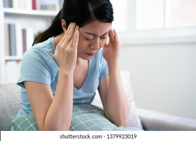 japanese mom woman suffering from headache sitting on couch holding pillow with frowning face. sick asian female at home resting not going to work with head stress hurting. illness wife indoors.