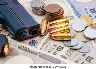 Japanese money JPY bill and coin with gun and bullet crime concept