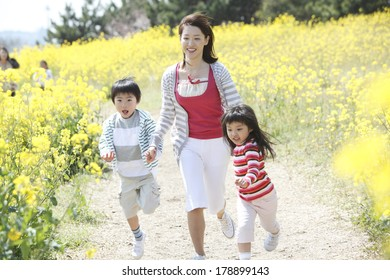 Japanese mother and children running in a rapeseed field