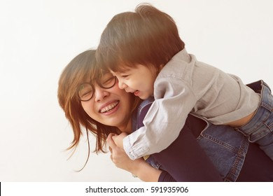 Japanese mother hugs her son, they laugh and smile. Warm family relations.