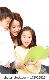 Japanese mother reading a book to her childen