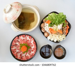 Japanese nabemono hot pot of thinly sliced meat, udon and vegetables boiled in water, Beef Shabu-Shabu on black pottery plate, isolated on white background