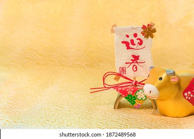 Japanese New Year's Card with handwriting ideograms Geishun or Welcoming Spring on a traditional decoration and a cute Zodiacal animal figurine of cow for the 2021 Year of the Ox on a felt background.