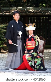Japanese newly wed couple in traditional wedding kimonos (the garden of Meiji-Jingu Shrine, Tokyo)