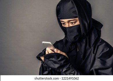 Japanese Ninja calling with smart phone.