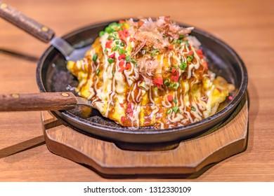 Japanese okonomiyaki covered with katsuobushi leek mayonnaise and bulldog sauce served on a hot plate with spatulas.