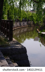 """Japanese old town view with willow tree, river and stone wall at Sawara, Japan.  Sawara is tourist site as it remains old architecture called """"Koedo"""" which means """"Small edo"""". Edo is Japanese old era."""