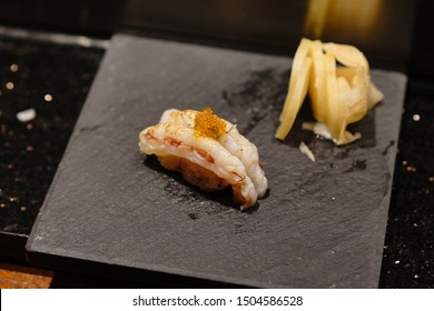 Japanese Omakase meal: Close up  Sushi served by hand with pickled ginger on glossy black plate. Japanese luxury meal.Japanese Omakase course.