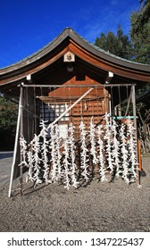 Japanese omikuji fortune paper tied on a line in at shinto shrines.