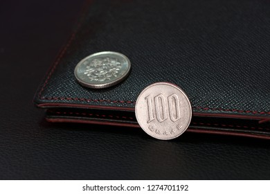 Japanese one hundred Yen coins on reverse (JPY) and out focus hundred Yen on obverse with black wallet on black floor, the concept of finance.