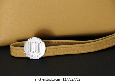 Japanese one hundred Yen coins on  reverse (JPY) with sand color wallet on black floor, the concept of finance.