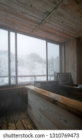 Japanese onsen traditional bathtub with open window and winter forest view