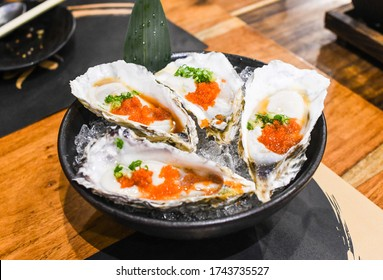 Japanese Oyster on ice garnished with tobiko fish roe in japanese restaurant
