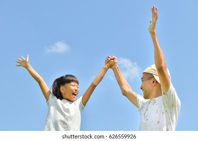 Japanese parent and child raise hands
