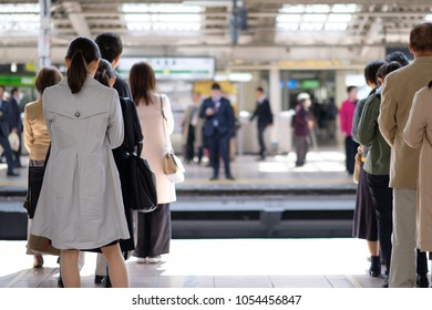 Japanese people queuing, waiting for their commuter train in a busy railway station in Tokyo on a bright spring day.