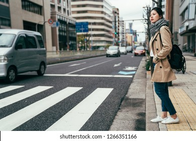 japanese people walking waiting for traffic lights to cross busy road with car driving through. Asian Chinese woman living in city in osaka. young lady standing on the street in spring wearing scarf.