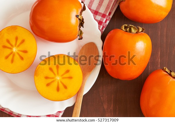 Japanese persimmon (Diospyros kaki) served on white plate. Top view