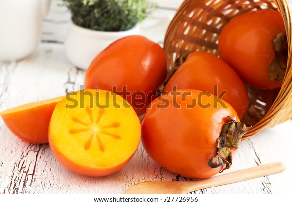 Japanese persimmon (Diospyros kaki) in woven basket on white rustic wooden background