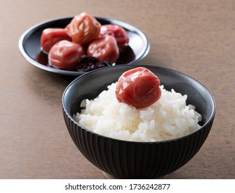 Japanese pickled plum and freshly cooked rice with one pickled plum