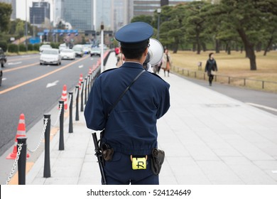 A Japanese police office using a megaphone in Tokyo on a cloudy day to control the foot traffic crowds as well as vehicular traffic while wearing his police belt with a baton and caution tape.