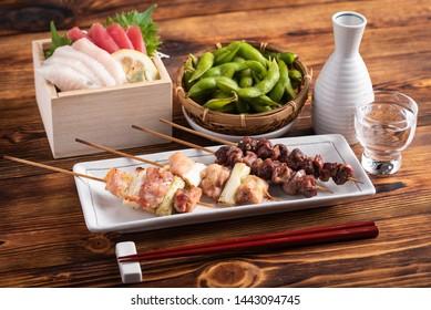 japanese popular izakaya food and sake, edamame, sashimi, yakitori