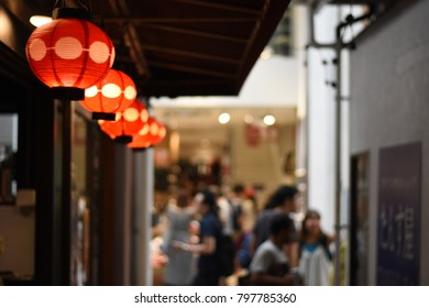 Japanese pub bar, izakaya sign, red paper lanterns hanging under the roof.