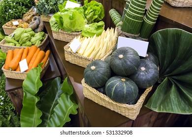 Japanese pumpkin and various vegetable on display shelf.