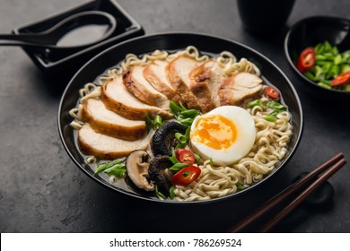 japanese ramen noodle with chicken, shiitake mushroms and egg in black bowl,selective focus