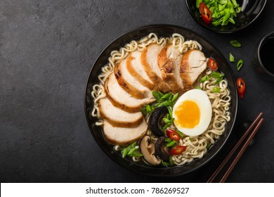 japanese ramen noodle with chicken, shiitake mushroms and egg in black bowl, top view