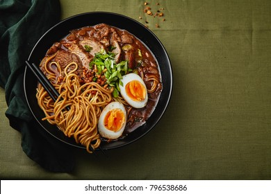 Japanese ramen with pork belly, mushrooms and marinated eggs on green linen tablecloth. Horizontal composition with copy space