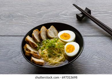 japanese ramen soup with chicken and boiled egg in black bowl