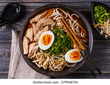 Japanese ramen soup with chicken, egg, chives and sprout on dark wooden background.