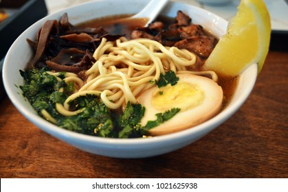 Japanese ramen soup with chicken, mushrooms and egg on a wooden tray. Miso ramen noodles. Asian food.