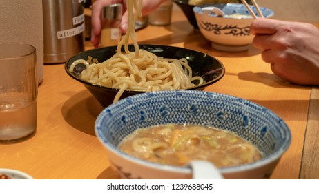 Japanese ramen soup with noodles in ceramic bowl on wood table background.