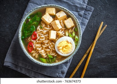 Japanese ramen soup with tofu and egg on dark stone background. Miso soup with ramen noodles and tofu in ceramic bowl, asian traditional food.