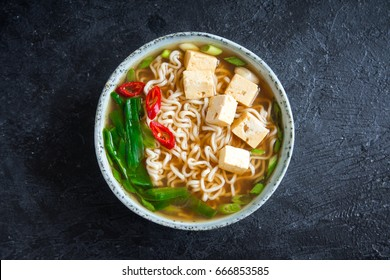 Japanese ramen soup with tofu on dark stone background. Miso soup with ramen noodles and tofu in ceramic bowl, asian traditional food.