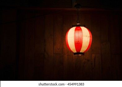 Japanese red lantern and light with wooden background