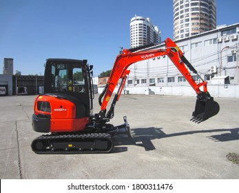 Japanese red mini excavator Kubota in a construction road vehicle parking lot, Krasnodar, Russia, August 19, 2020. A hoisting machine with a digging bucket and track wheels. Side view.