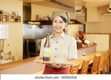 Japanese restaurant clerk carries the beer