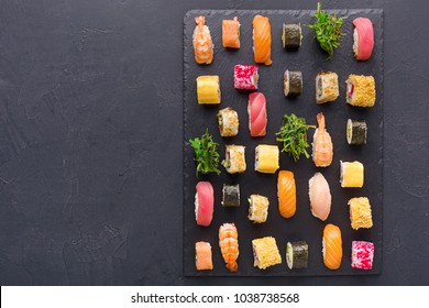 Japanese restaurant, sushi roll platter on black slate plate. Set for one person, top view, copy space