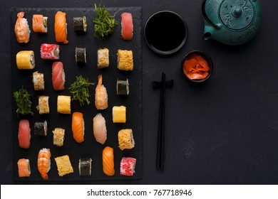 Japanese restaurant, sushi roll platter on black slate plate. Set for one person, with chopsticks, ginger, soy, top view