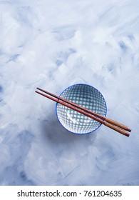 Japanese rice bowl and chopsticks on blue background