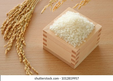 Japanese rice in a wooden square cup with some fresh ear of rice