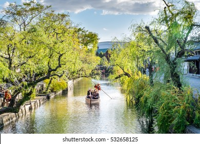 Japanese rowing boats with tourists, lake city japan at Kurashiki Bikan Historical Quarter,Passenger on the Traditional Boat Tour of Kurashiki Canal Sailing  through the center of town